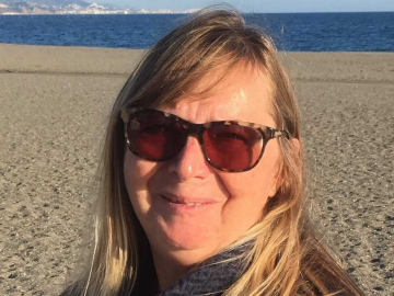 Debbie Flay smiling on a beach.